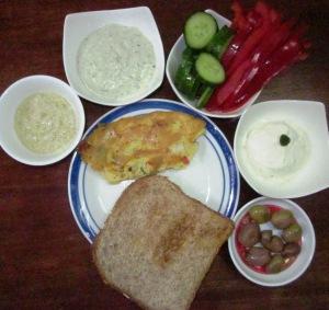 הצעת הגשה (עם כיוון השעון): ממרח ארטישוק, טחינה עם בזיליקום, ירקות חתוכים, גבינת טופו, זיתים, לחם קסטן ואומלט טבעוני